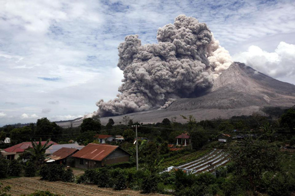 Mount Sinabung releases pyroclastic flows seen from Tiga Serangkai, North Sumatra, Indonesia, Wednesday, April 1, 2015. Mount Sinabung, among about 130 active volcanoes in Indonesia, has sporadically erupted since 2010 after being dormant for more then 400 years. (AP Photo/Binsar Bakkara)